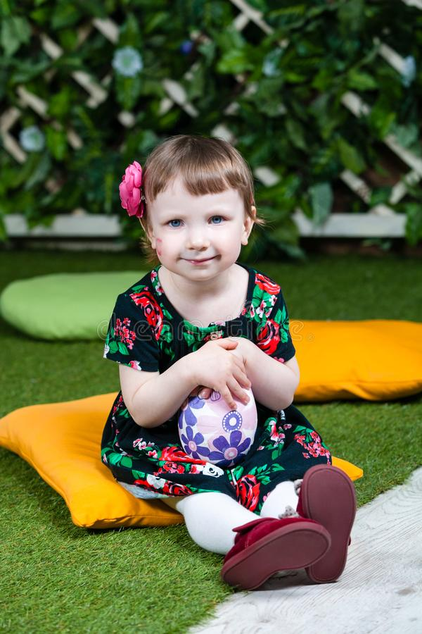 Easter holiday. Cute little girl holding an easter egg. Ivy wall in background. Vertically framed shot stock photography