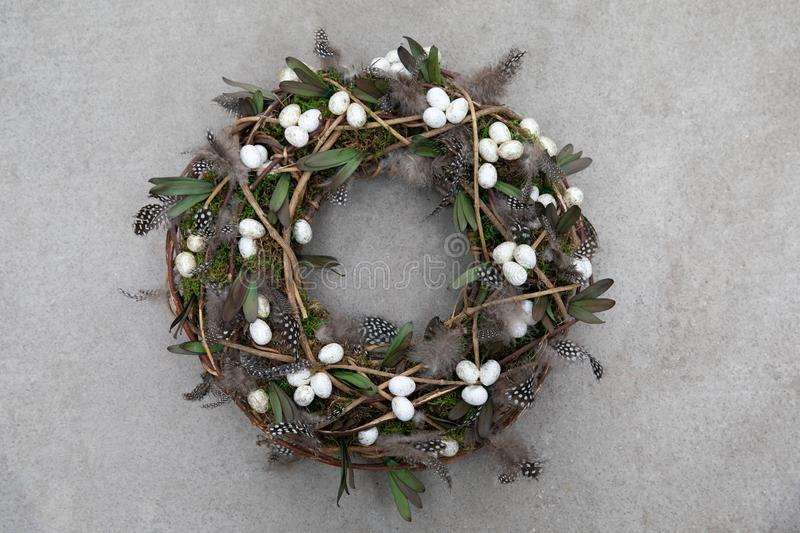 Easter holiday decor handmade wreath-stylish composition of feathers, eggs, green leaves for your home door decoration. Isolated on a gray concrete background royalty free stock photography