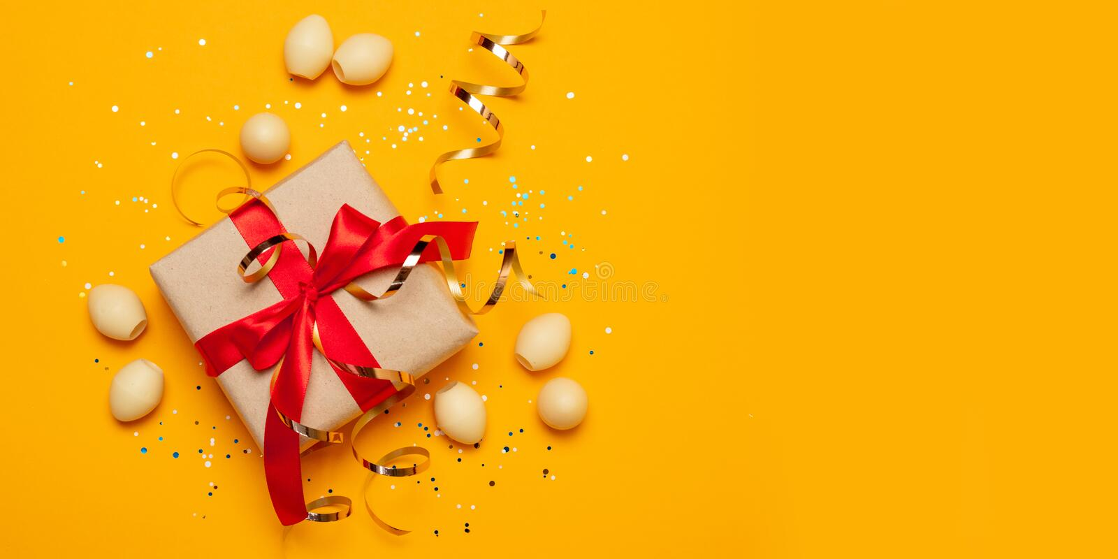Easter concept background of gift or present box with red atlas ribbon and stars confetti on yellow background.Holiday decorations. Easter holiday decorations royalty free stock photography
