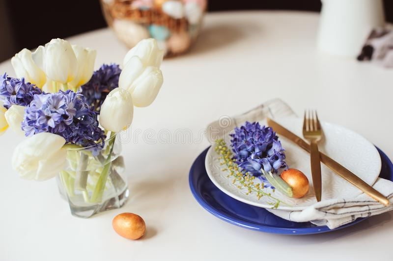 Easter holiday festive dining table with plate, golden cutlery, painted eggs and hyacinth flower on white background royalty free stock images