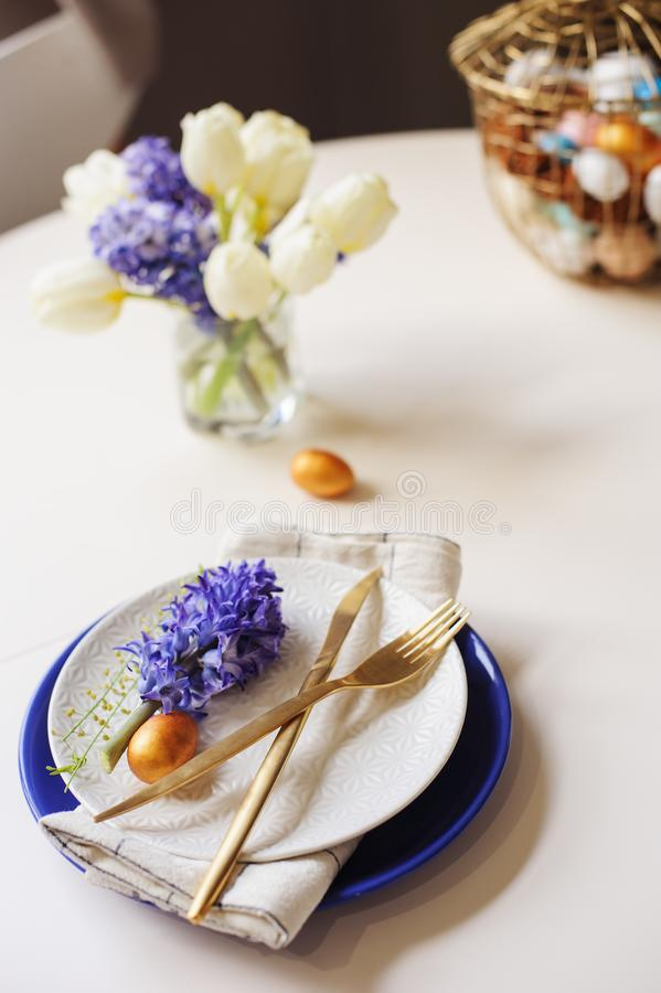 Easter holiday festive dining table with plate, golden cutlery, painted eggs and hyacinth flower on white background royalty free stock photo