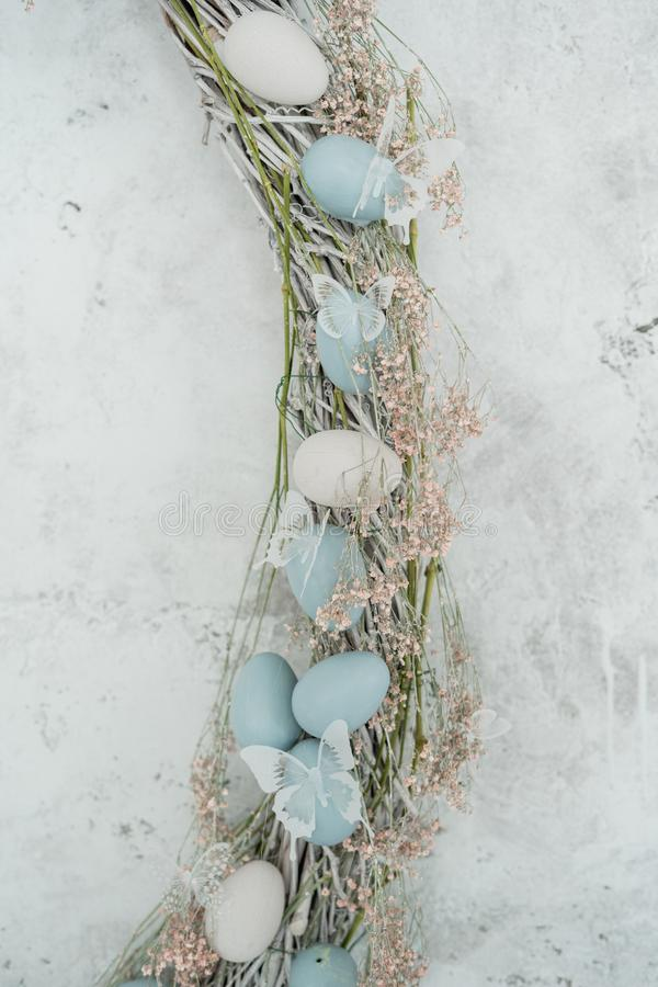 Easter Holiday Egg Floral Wreath Flat Lay Decor. Happy Celebration in Elegant Blue Pastel Decoration. Traditional Empty Shabby Wall Layout Detail. Decorative stock photo