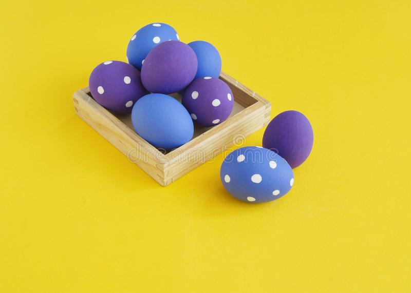 Easter holiday. Easter eggs in a tray for eggs. Eggs on a stand. Yellow background. stock image