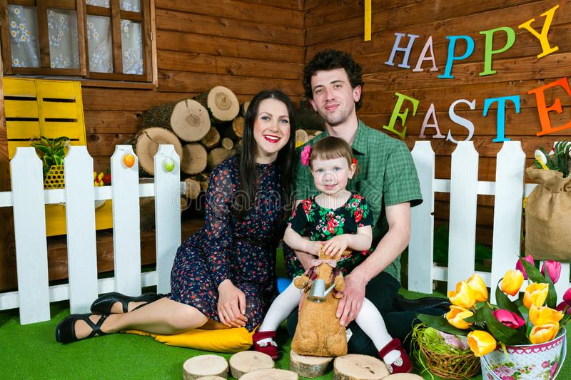 Easter holiday. Family portrait. Girl holding an Easter Bunny. On the wall the writing Happy Easter. Horizontally framed shot royalty free stock photo