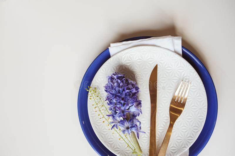 Easter holiday festive dining table with plate, golden cutlery and hyacinth flower on white background royalty free stock photos