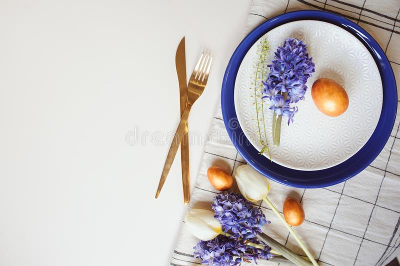 Easter holiday festive dining table with plate, golden cutlery, painted eggs and hyacinth flower on white background royalty free stock image