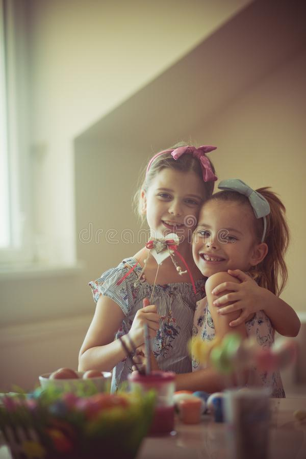 Easter is a holiday full of love and happiness. Little girls coloring Easter egg royalty free stock photo