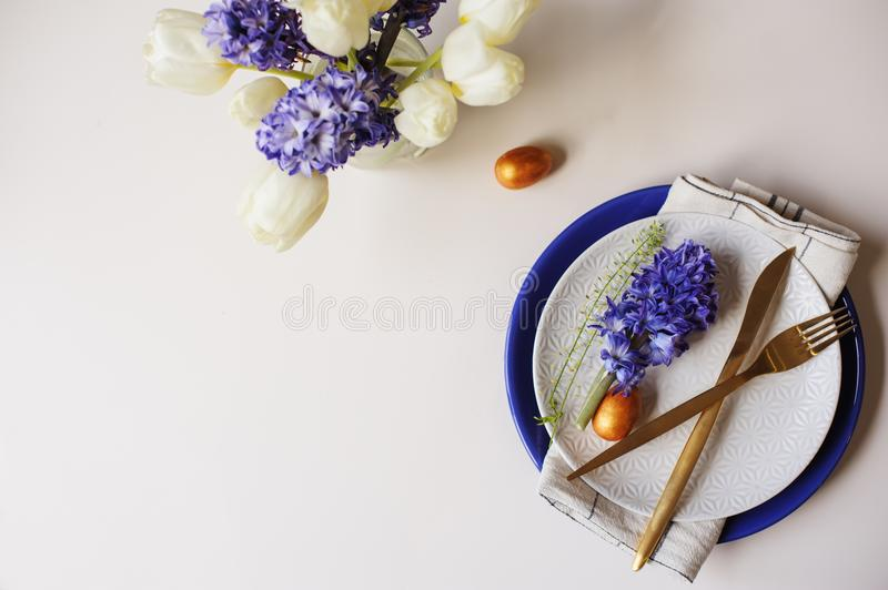 Easter holiday greeting card, dining table with plate, golden cutlery, painted eggs and hyacinth flower on white background royalty free stock image