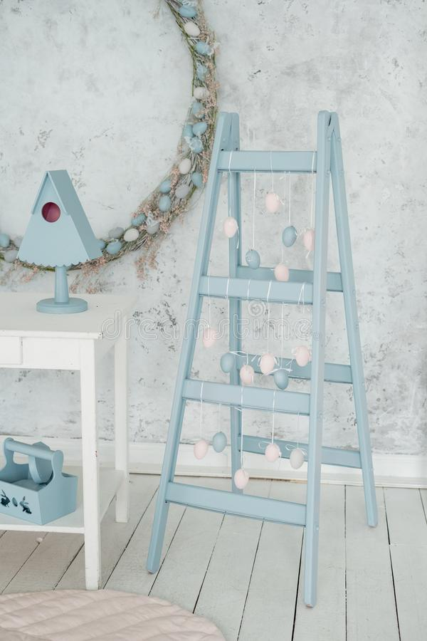 Easter Holiday Interior Decor Blue Ladder and Egg. Garland Background. Happy Celebration in Elegant Pastel Studio Decoration. Empty Vertical Cement Wall Copy stock photos