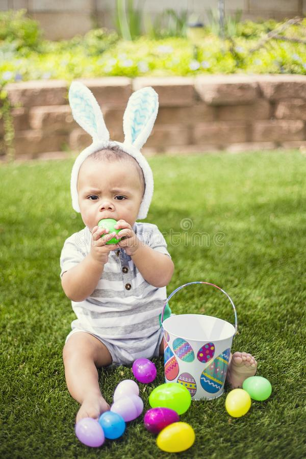 Cute little boy in trying to eat a plastic Easter egg. Easter Holiday lifestyle photo. Cute little boy trying to swallow a plastic Easter egg he found while on royalty free stock photos