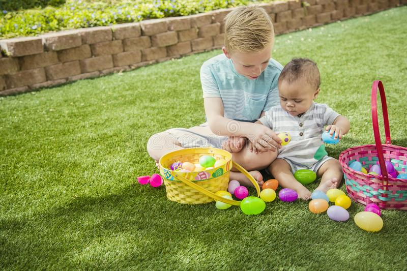 Two Cute little boys collecting eggs on an Easter Egg hunt outdoors. Easter Holiday lifestyle photo. Two Cute little boys collecting eggs on an Easter Egg hunt royalty free stock image