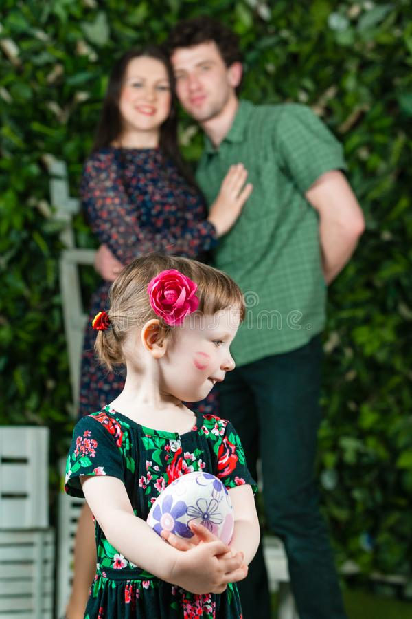 Easter holiday. Little girl playing with Easter egg. Parents are in background. Mother kissed daughter on cheek. Vertically framed shot royalty free stock photos