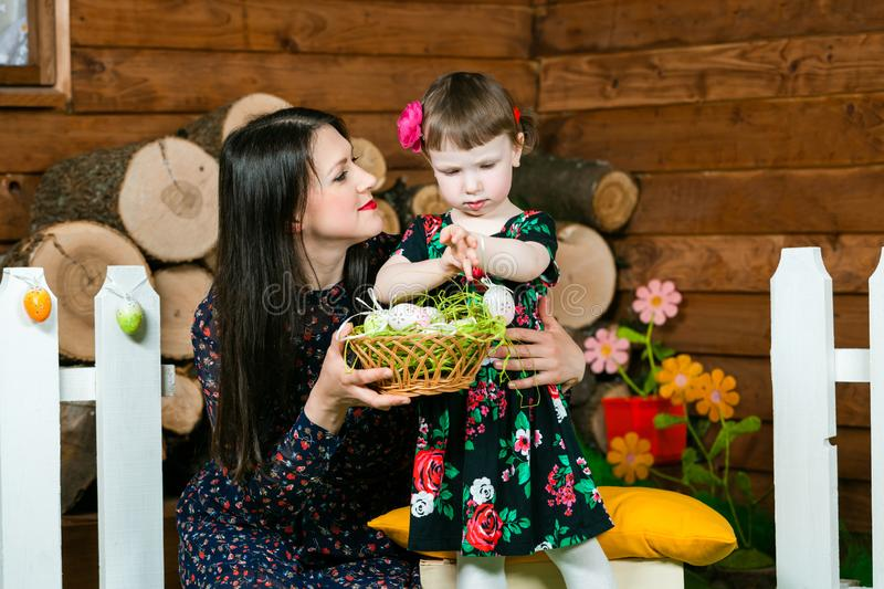 Easter holiday. Mom and daughter play with Easter eggs. In background is a village house. Horizontally framed shot royalty free stock image
