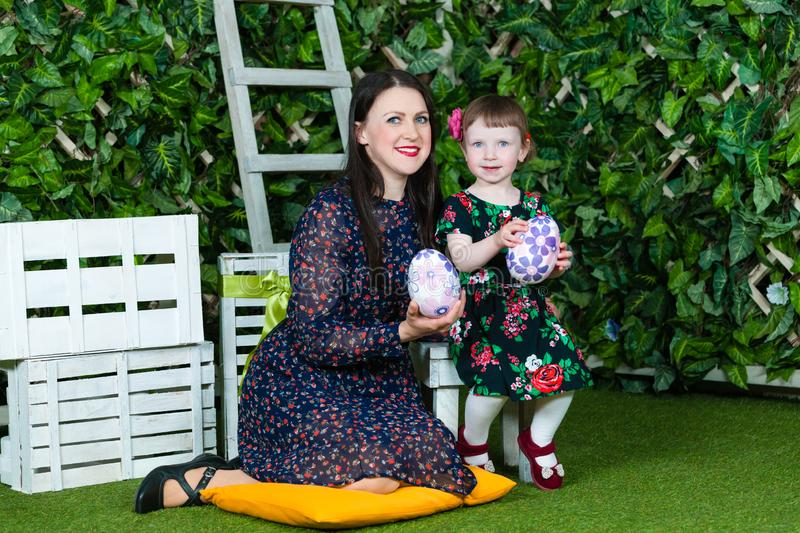 Easter holiday. Mom and daughter play with Easter eggs. Ivy wall in background. Horizontally framed shot royalty free stock images
