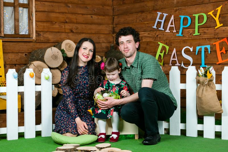 Easter holiday. Parents and daughter play with Easter eggs. On the wall the writing Happy Easter. Horizontally framed shot royalty free stock photo
