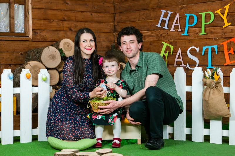 Easter holiday. Parents and daughter play with Easter eggs. On the wall the writing Happy Easter. Horizontally framed shot stock images