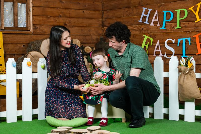 Easter holiday. Parents and daughter play with Easter eggs. On the wall the writing Happy Easter. Horizontally framed shot stock photography