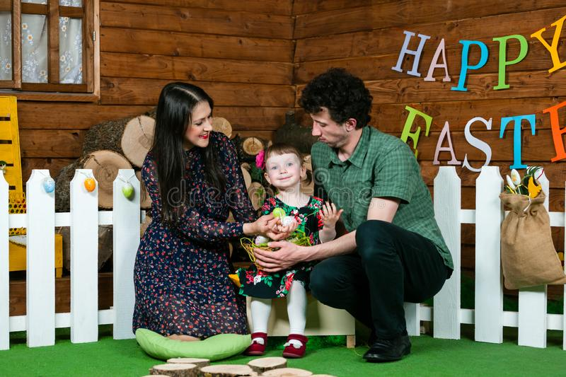 Easter holiday. Parents and daughter play with Easter eggs. On the wall the writing Happy Easter. Horizontally framed shot royalty free stock image