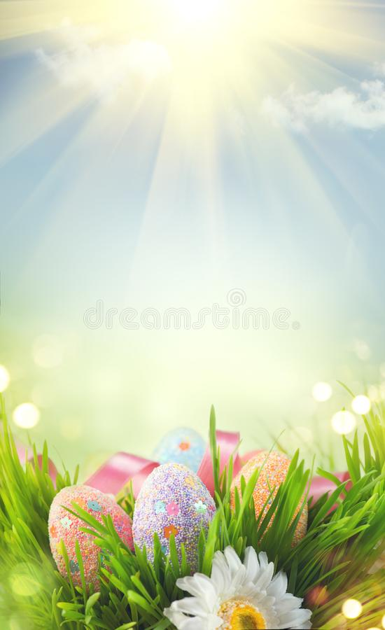 Easter holiday scene background. Traditional painted colorful eggs in spring grass over blue sky royalty free stock images