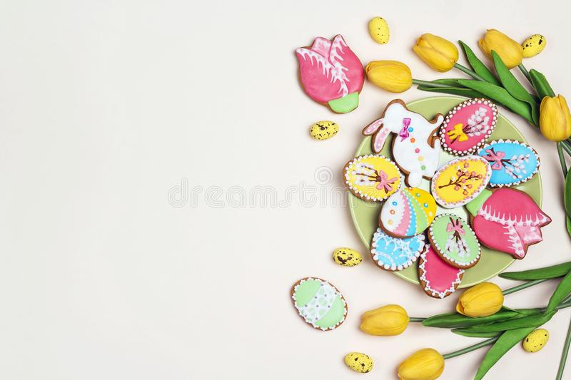 Easter homemade gingerbread cookies on a light background with tulips and copy space stock photo