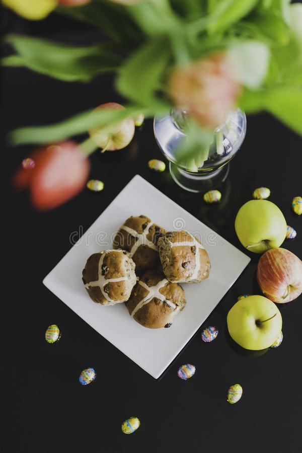 Easter hot cross buns and chocolate eggs with apples and flowers royalty free stock photo