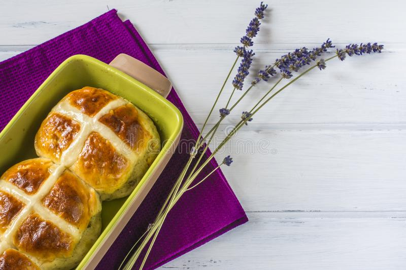 Easter hot cross buns with lavender flowers on napkin and wooden white table. royalty free stock image