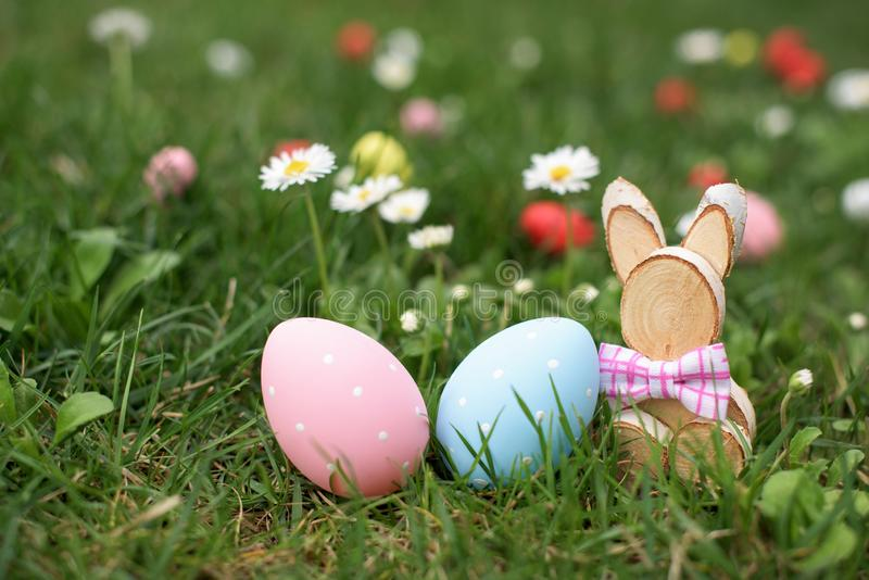Easter hunt -blue and pink hen eggs and wooden bunny in a grass stock images