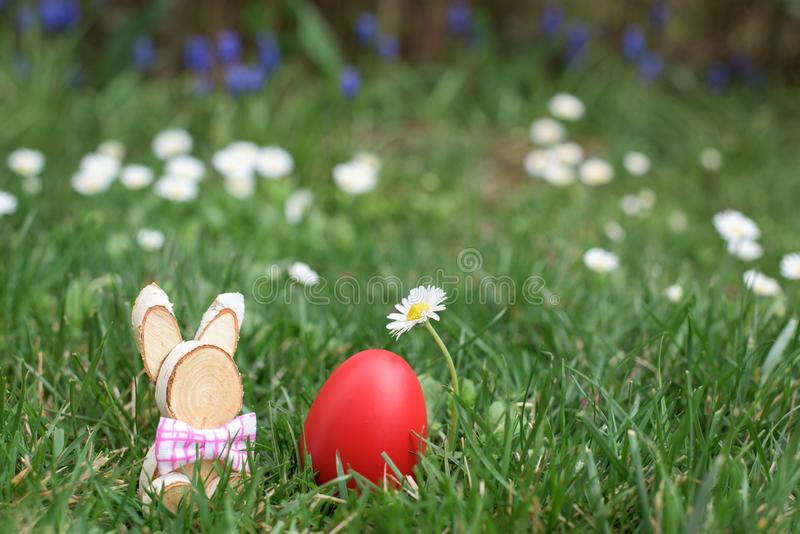Easter hunt - red egg and wooden bunny royalty free stock photography