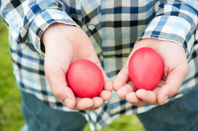 Easter hunt - two red eggs in hands royalty free stock photography