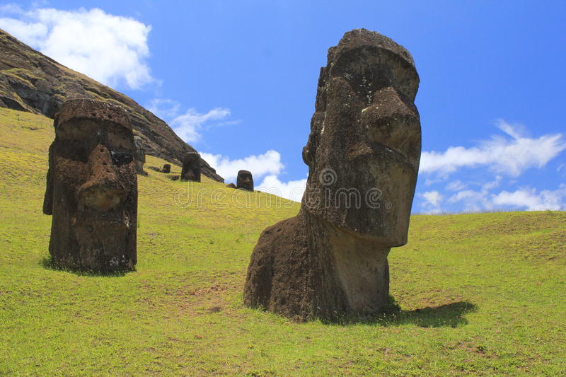Easter Island Moais. Moais heads burried in the the Moai Factory in Easter Island. Blue sky and some clouds behind the mountain stock images