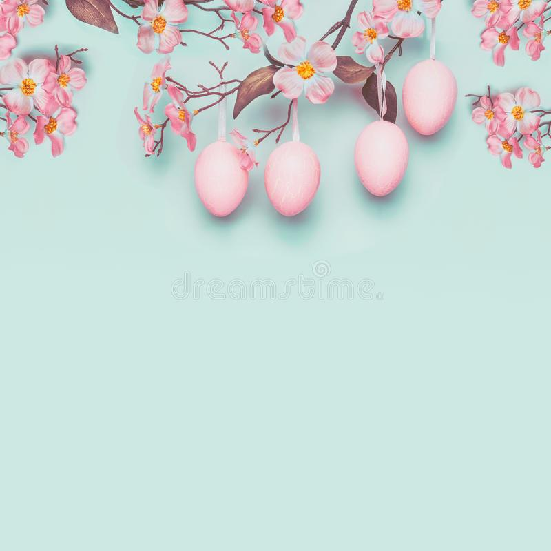 Easter layout with hanging pastel pink eggs and spring blossom at light at blue turquoise background stock photos