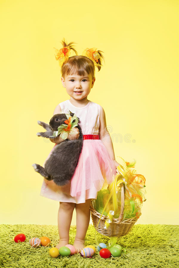 Easter little girl, child bunny rabbit and eggs. Easter little girl, child holding bunny rabbit basket eggs over yellow background royalty free stock photos