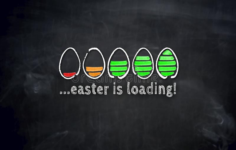 Easter is loading concept with eggs on blackboard stock image