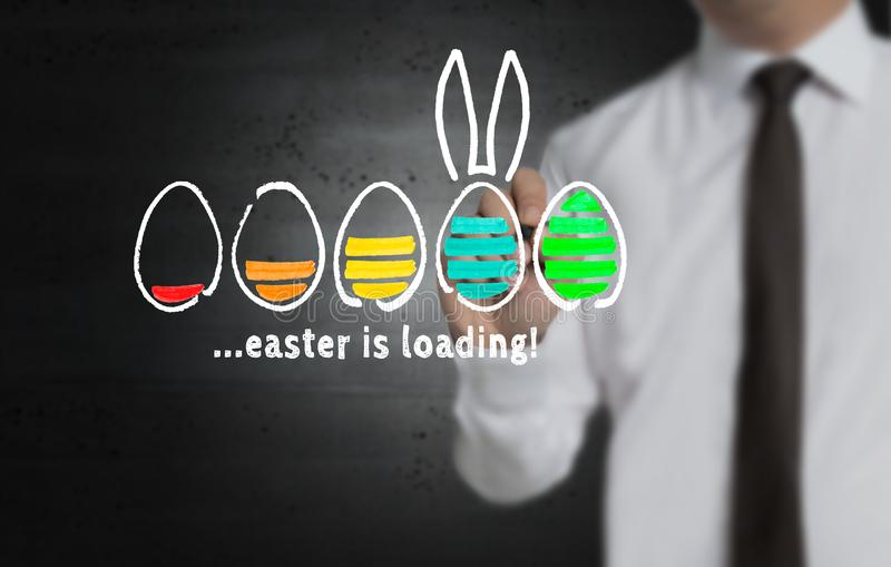 Easter is loading is written by businessman on screen royalty free stock images