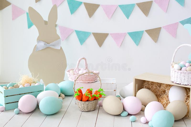Easter! Many colorful Easter eggs with bunnies and baskets! Easter decoration of the room, children`s room for games. Basket with stock images