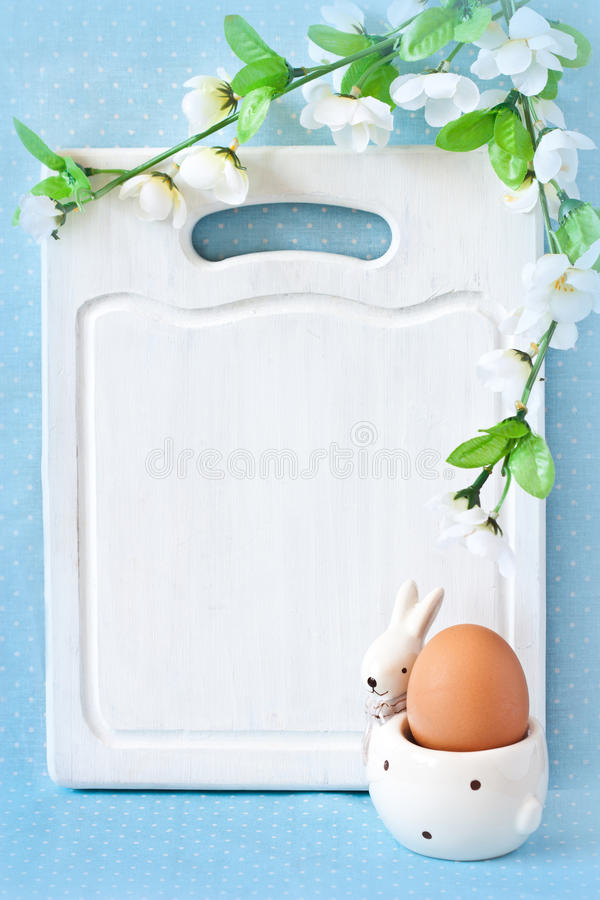 Easter menu. Old white kitchen cutting board with copy-space for writing Easter menu, funny rabbit egg cup and blossom apple tree stock photography