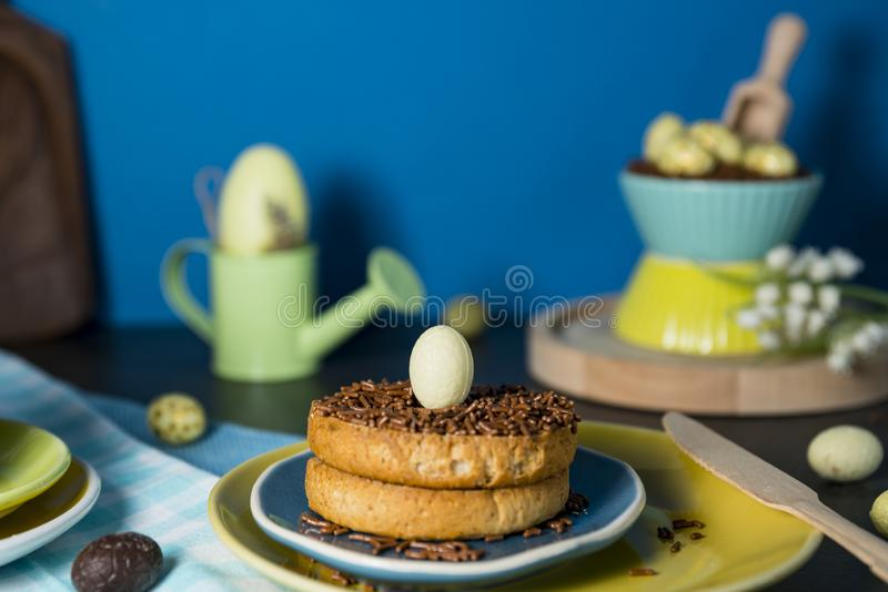Rusk with Dutch chocolate hail and chocolate Easter eggs, on blue plate. Easter morning scene with rusk and chocolate hail hagelslag, and chocolate eggs royalty free stock image