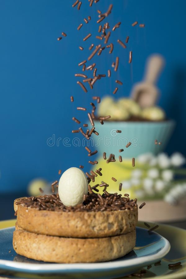 Rusk with Dutch falling chocolate hail and chocolate Easter eggs. Easter morning scene with rusk and falling chocolate hail hagelslag, and chocolate eggs stock photography