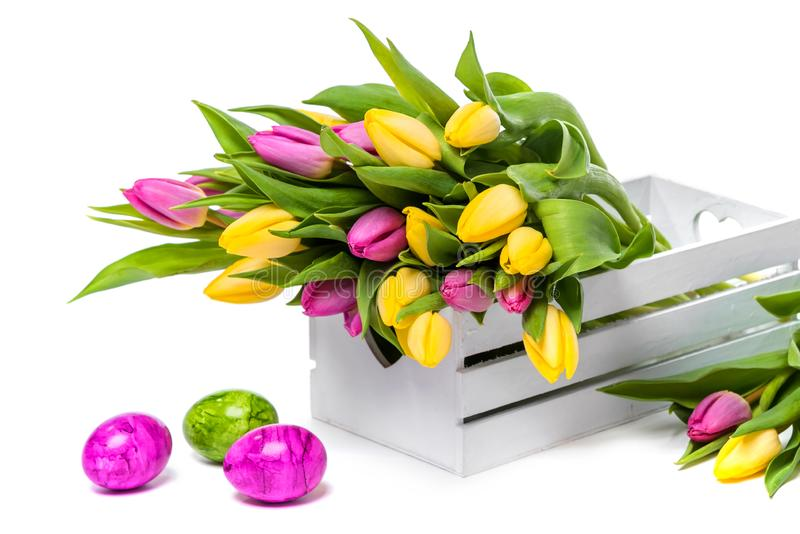 Easter eggs and a bunch of colorful tulips in a white wooden box on a white background royalty free stock photography