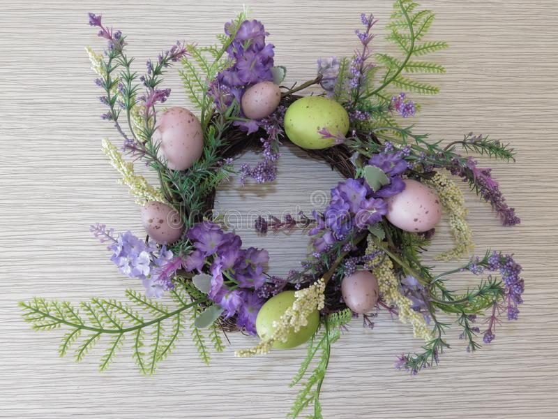 Easter nest shaped basket of green blue purple flowers and colorful eggs on grey background. Quail eggs. stock photos
