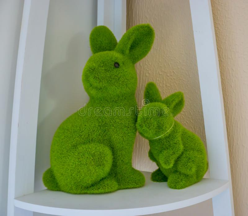 Easter one big green stuffed bunny with stuffed baby rabbit decoration on a shelf. Easter decoration one big green stuffed bunny with stuffed baby rabbit stock images