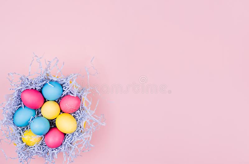 Easter painted eggs in fun blue nest on soft pink background, copy space, top view. Easter painted eggs in fun blue nest on soft pink background, copy space stock photo