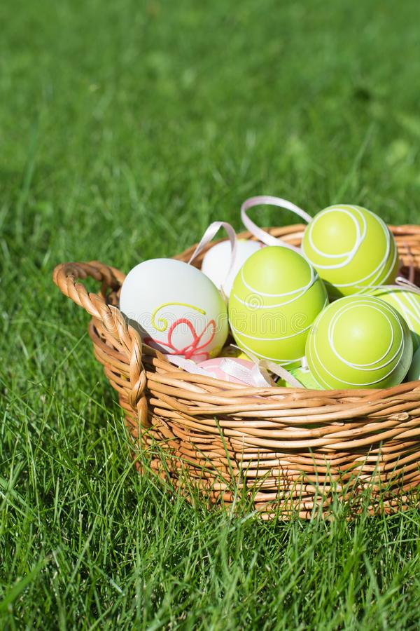 Easter painted pastel color eggs with ribbon in basket on green grass. Sunny day. Close up. Selective focus. royalty free stock photos
