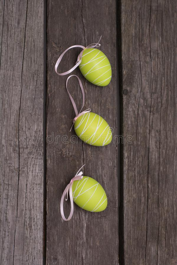Easter painted pastel green eggs with ribbon on wooden board. Concept. Top view. stock photos