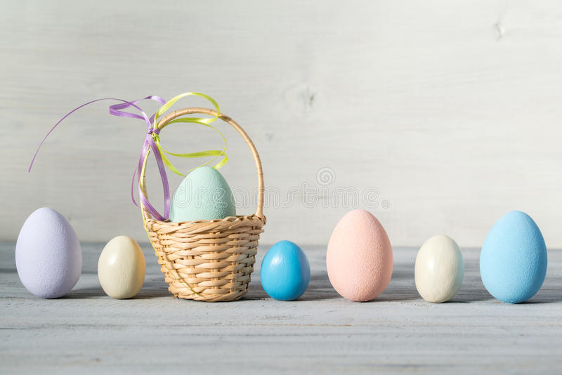 Easter pastel colored eggs and small basket on a light wooden background. Easter pastel colored eggs and small basket with egg on a light wooden background royalty free stock image