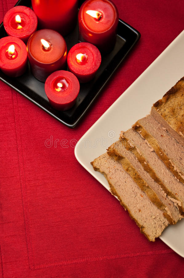 Easter pate food composition. Still life food composition with red color theme of pate dish and lit candles royalty free stock image