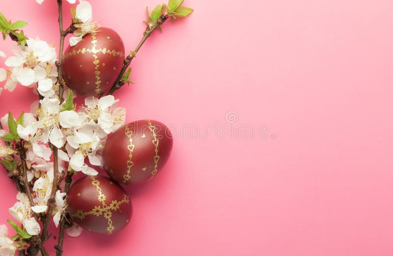 Easter pink background with Easter eggs and spring flowers. Top view with copy space royalty free stock photos