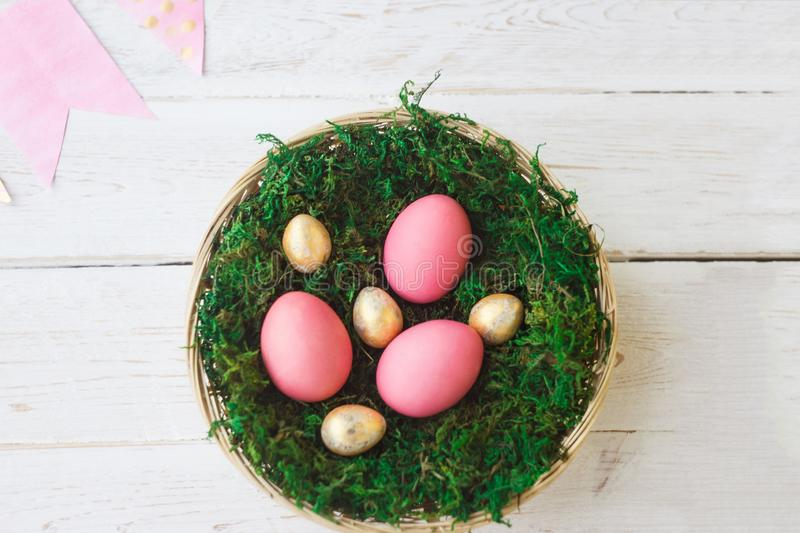 Easter. Pink and gold Easter eggs lie in a nest with moss on a white wooden background with a decoration of paper garland. Spring stock photos