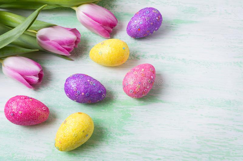 Easter pink, purple, yellow glitter eggs and tulips, copy space stock photo