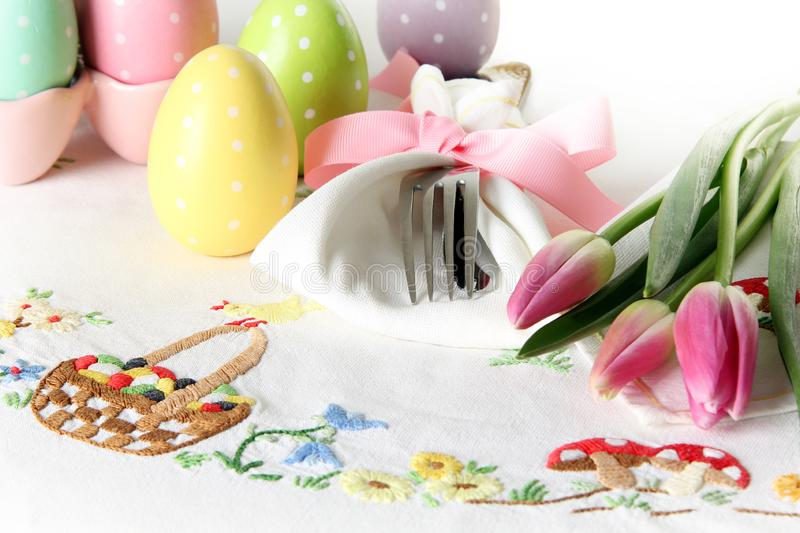 Easter place setting on an elegant linen table cloth. This traditional holiday brunch place setting includes painted eggs, an royalty free stock image